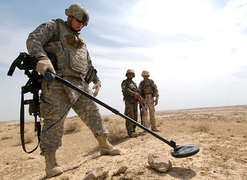 Photograph shows a soldier with the metal detector in one hand.