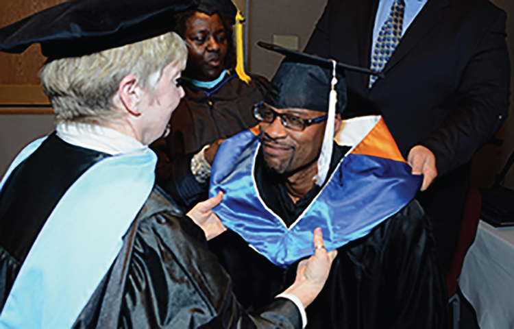 A photograph of a graduate during a college graduation ceremony.