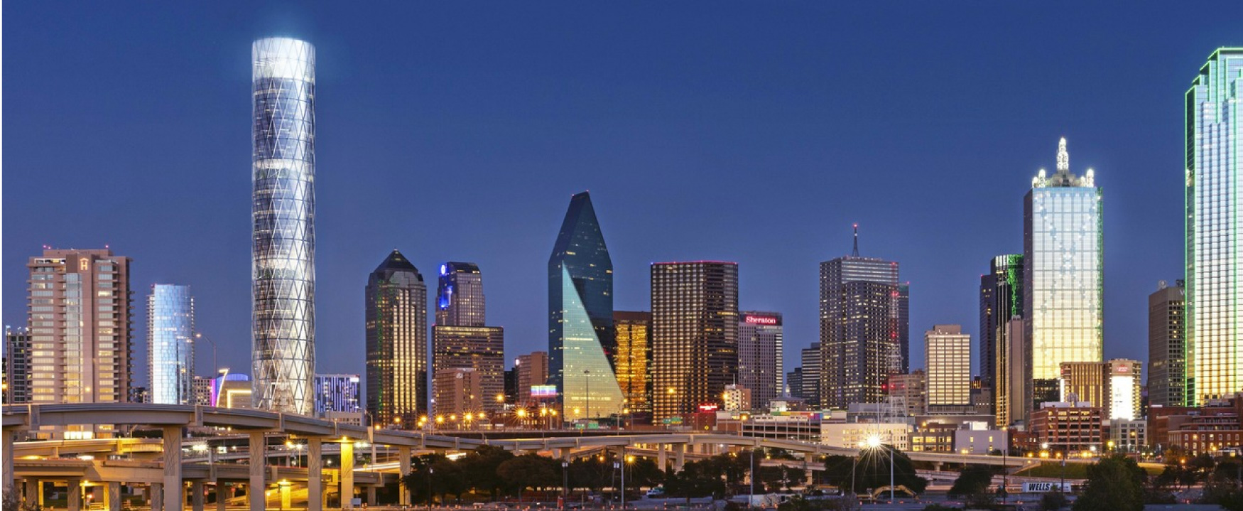 A photograph shows a brightly lit city skyline. Many of the buildings appear to be newly constructed and made entirely of glass.
