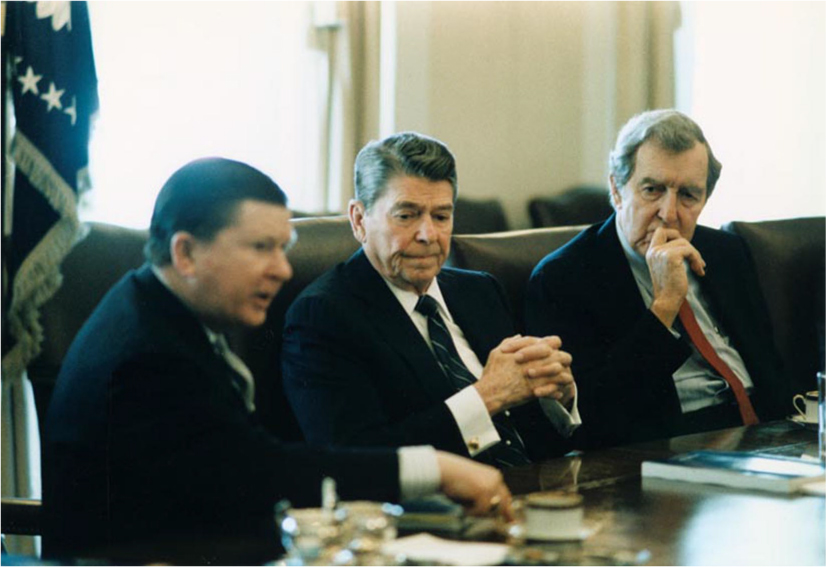 President Ronald Reagan sits at a table between Edmund Muskie and John Tower.