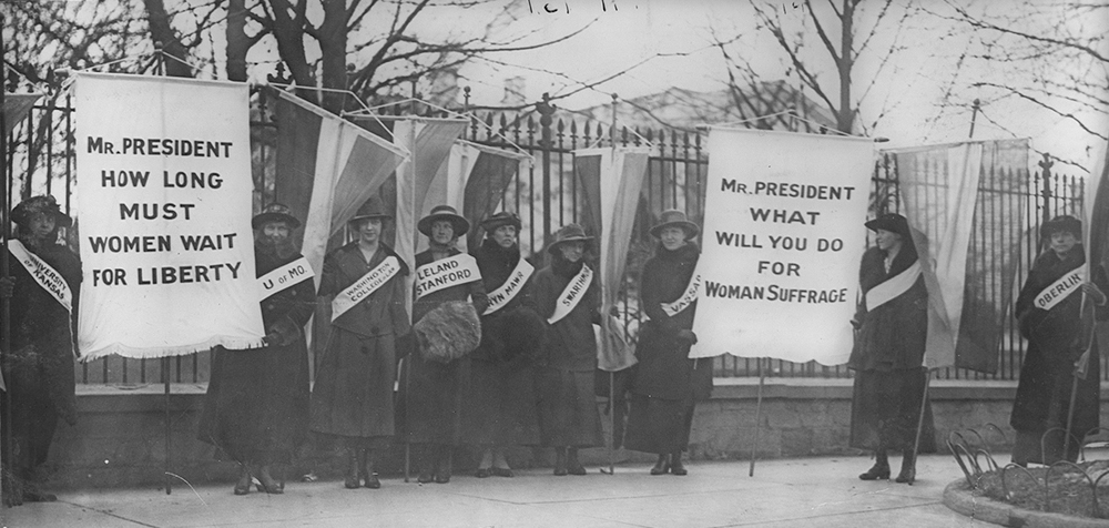 Figure (a) shows women's suffrage marchers.