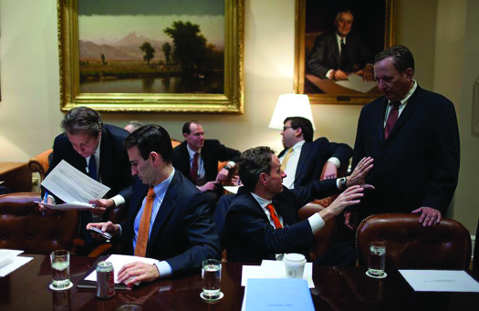 An image of seven people seated around a room. Some are talking to each other. Some are examining papers.