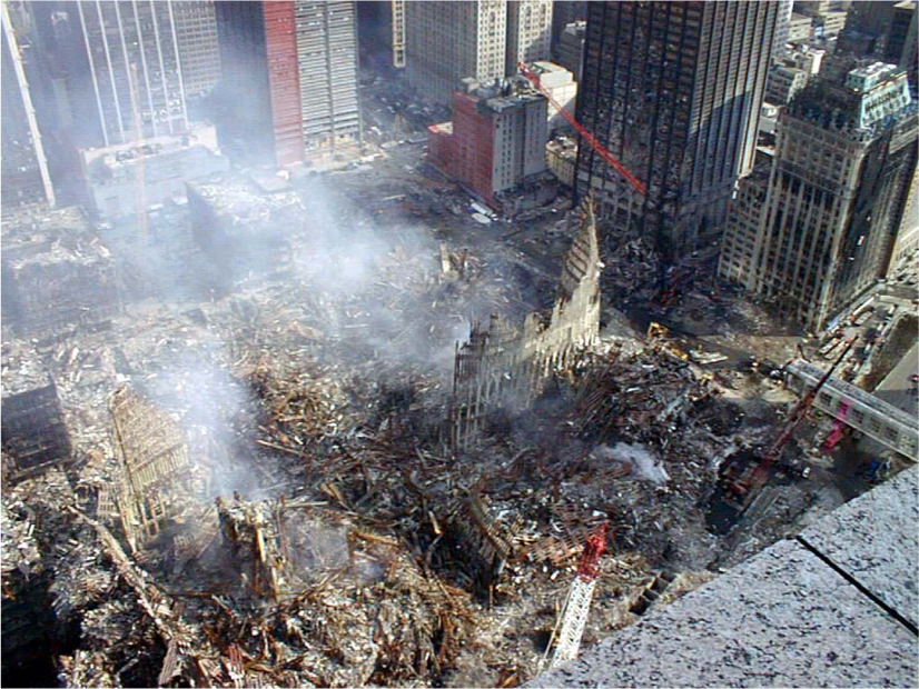 An aerial photograph of debris covering the ground in the middle of several skyscrapers. Smoke rises into the air.