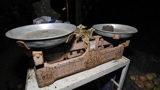An old rusted double-pan balance is shown with a weighing stone on one pan.