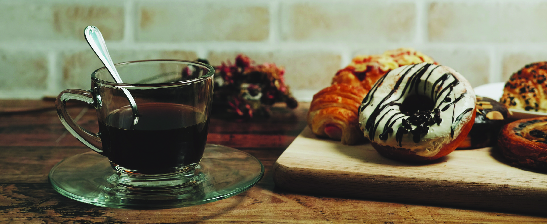 Picture of a cup of coffee beside a board with various pastries.