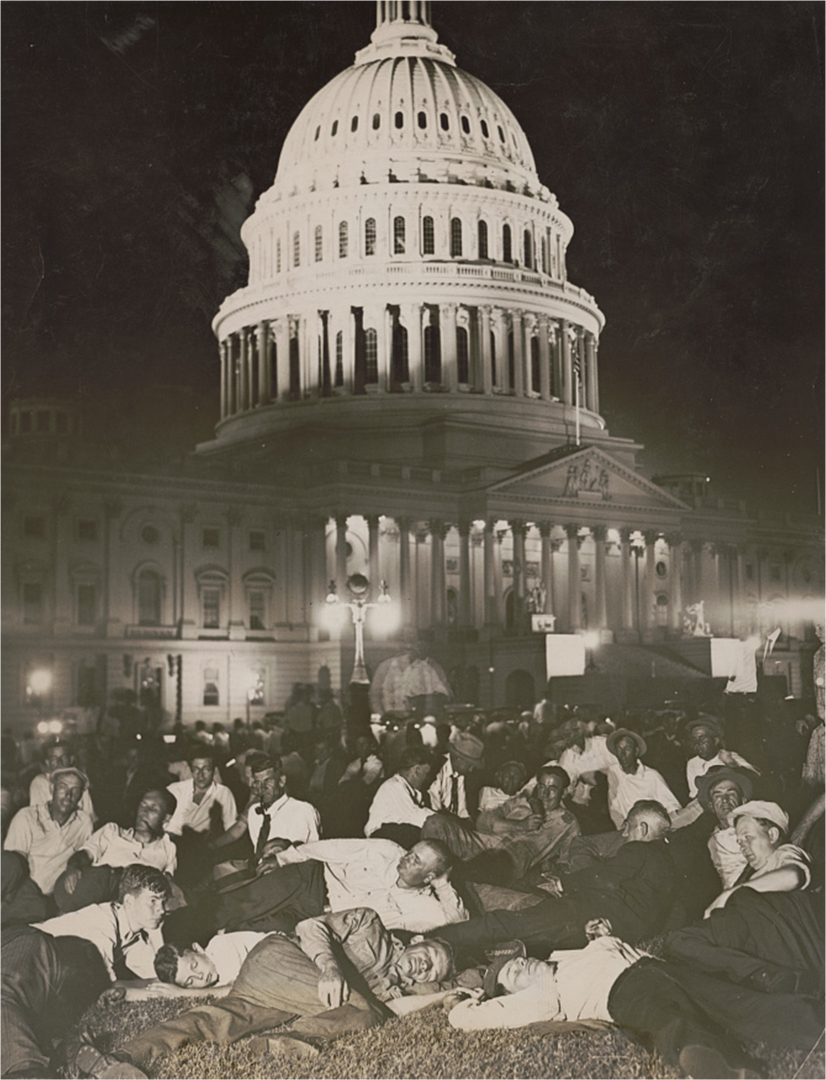 A crowd of men lies on the lawn in front of the Capitol at night.