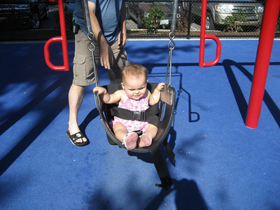 In the figure shown, a small child is seated in a spring swing, tied with a belt at his waist. In the back is his father, who is pushing the swing in the to and fro motion.