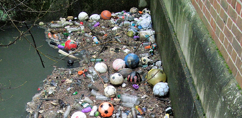 A photo of garbage that is washed up against a concrete wall.
