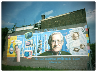 "A photograph shows a mural on the side of a building. The mural includes Chomsky's face, along with some newspapers, televisions, and cleaning products. At the top of the mural, it reads ""Noam Chomsky."" At the bottom of the mural, it reads ""the most important intellectual alive."""