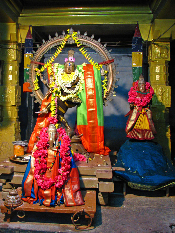 Three statues of Hindu gods garlanded with flowers are seen inside a temple setting.