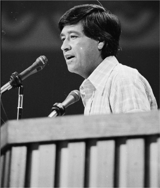 Cesar Chavez stands behind a podium and talks into a microphone.