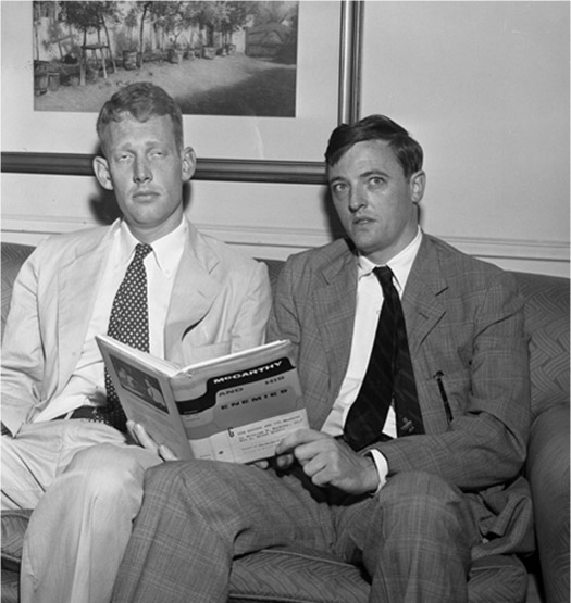 Brent Bozell and William Buckley sit on a couch and prop up their book McCarthy and His Enemies.