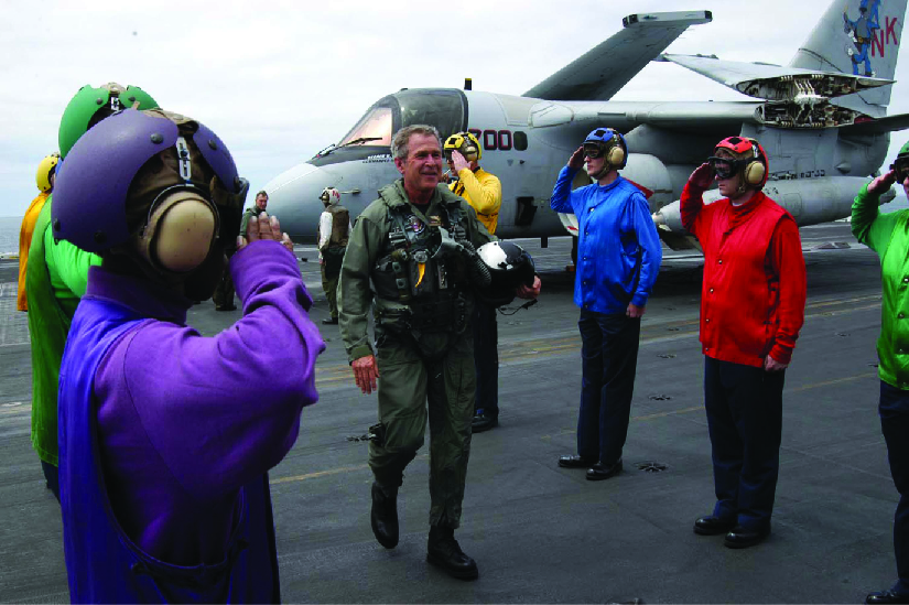A photo of George W. Bush in a flight suit stepping out of a plane onto an aircraft carrier. Personnel stand on either side and salute him.
