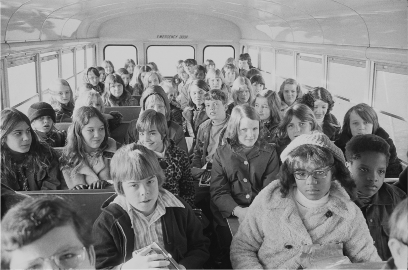 School children sit on a school bus. A row of black children is in the foreground.