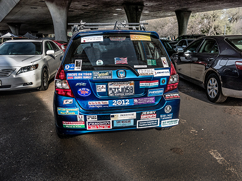 A photograph shows the back of a car that is covered in numerous bumper stickers.