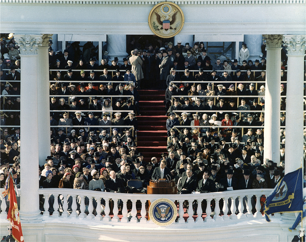 President Kennedy stands behind a podium and delivers a speech from the balcony of the Capitol. A crowd sits behind him.