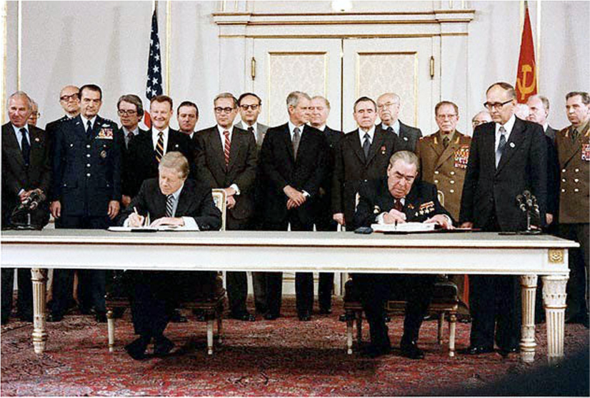 President Jimmy Carter and Soviet leader Leonid Brezhnev sit at a table and sign documents. Officials stand behind them.