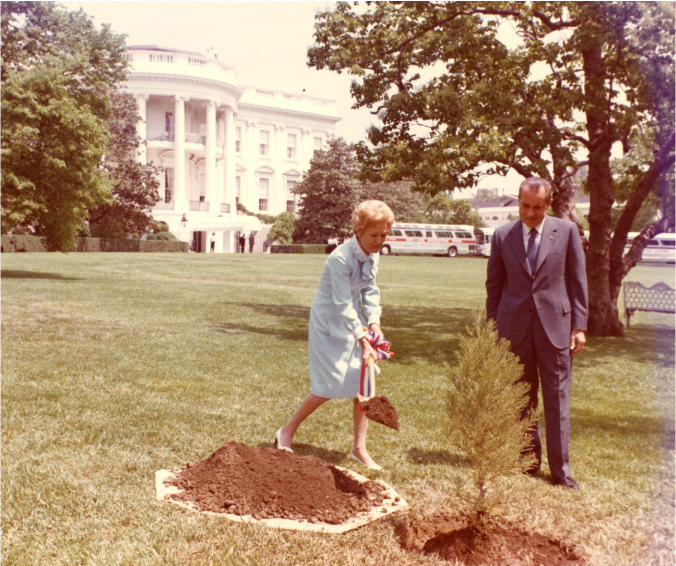 Pat Nixon adds a shovel of dirt around a small tree. Richard Nixon looks on. The White House is in the background.