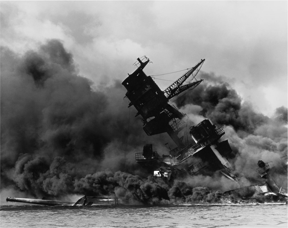 A ship is tilted halfway on its side. It is covered in smoke.