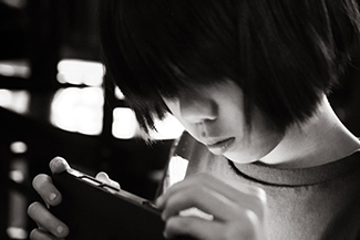 A photograph shows a young person looking at a handheld electronic device.