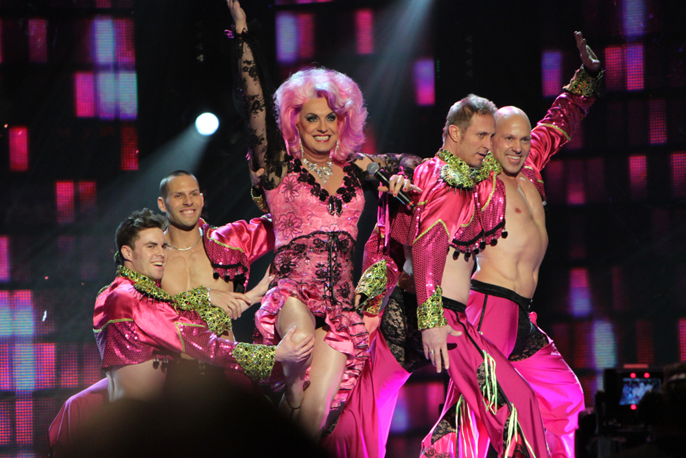 Five men dressed in pink drag attire, one in drag, are shown here.