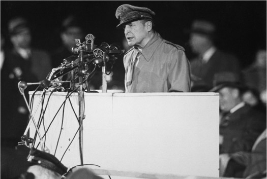 MacArthur delivers a speech behind a podium.