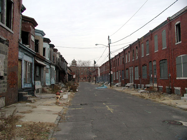 A block of run-down, dirty rowhouses is shown.