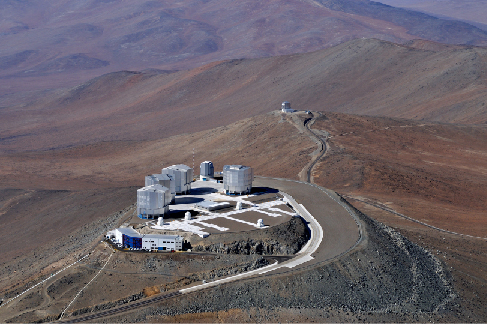 Photograph of four telescope buildings of the European Southern Observatory's Very Large Telescope array, taken at night. In the distance, the building holding VISTA is visible.