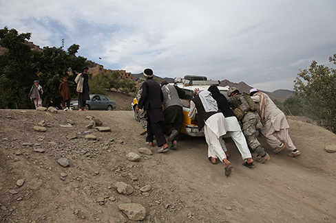 A photograph shows several people pushing a car up an incline.
