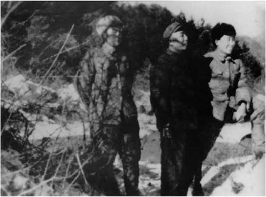 Three men wearing uniforms stand outside.
