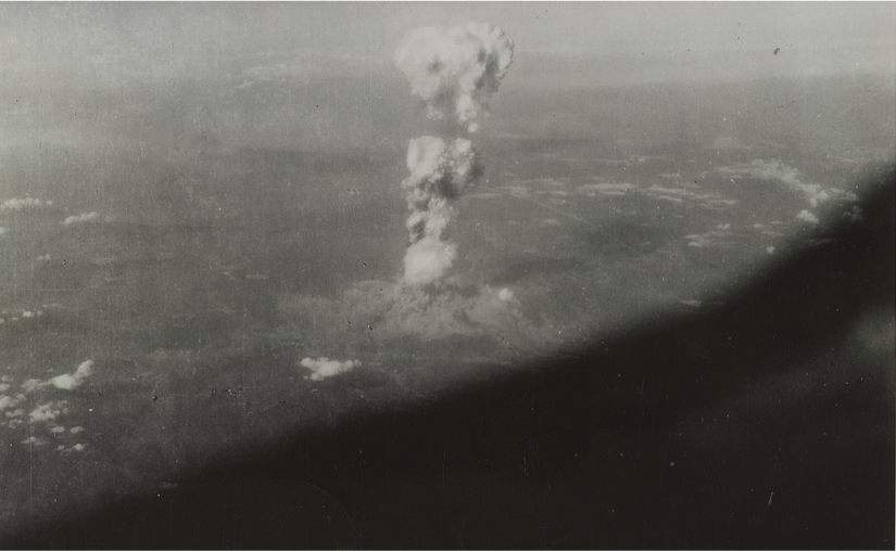 An aerial view of a large skinny cloud coming from the ground and rising to the sky. A cloud of dust spreads on the ground.