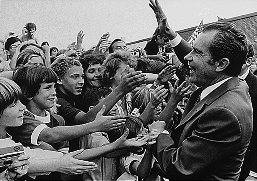 A crowd of children stick their right hands out towards President Nixon who waves and holds one child's hand.