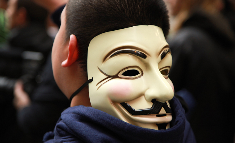 Photo of a man with a mask turned backwards around his head.