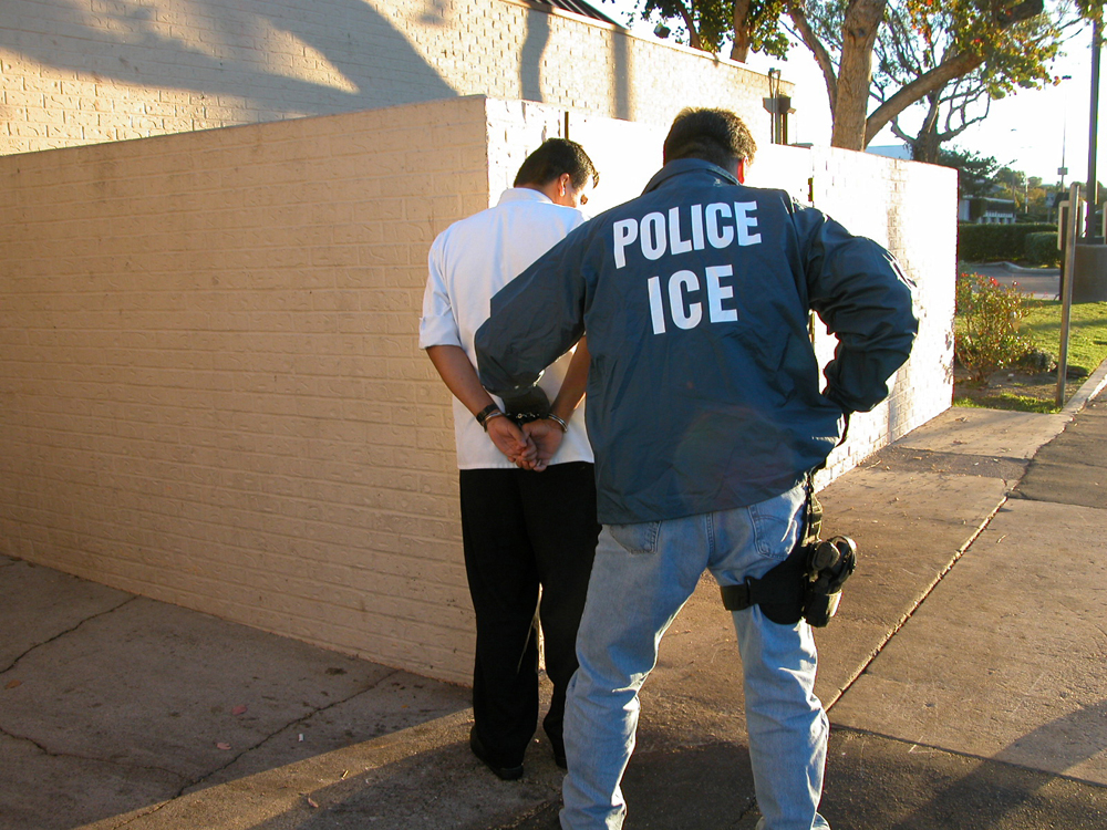 A police officer is shown cuffing a suspect.