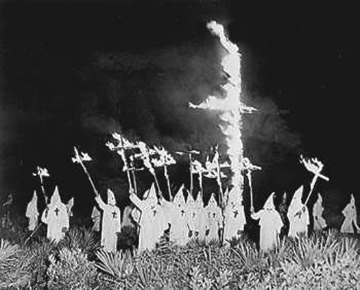 A photo of a group of people wearing robes and pointed hats, surrounding a large cross in the ground that is on fire. Several people hold burning crosses aloft.