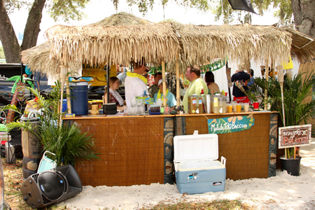 Several people in colorful T-shirts and leis are shown talking and drinking in an outdoor tiki bar setting.