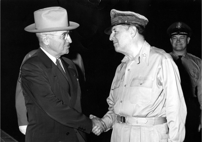 President Truman and General MacArthur shake hands.
