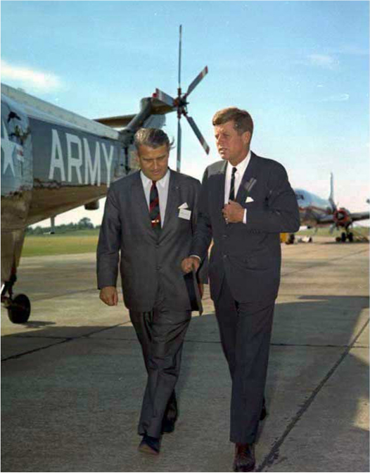 President John F. Kennedy walks with Werner Von Braun on a runway. Military planes are behind them.