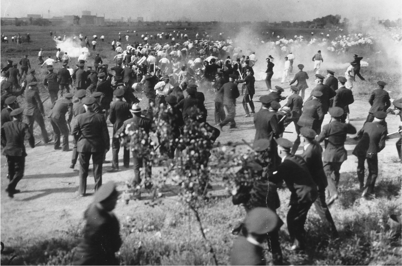 Many police officers stand in the foreground, looking towards civilians who are running away. Smoke is in between the two groups.
