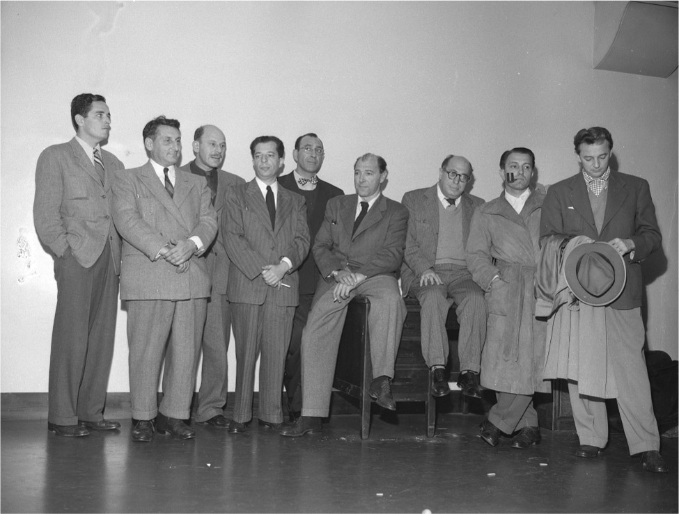A group of nine men in suits stand in a row.