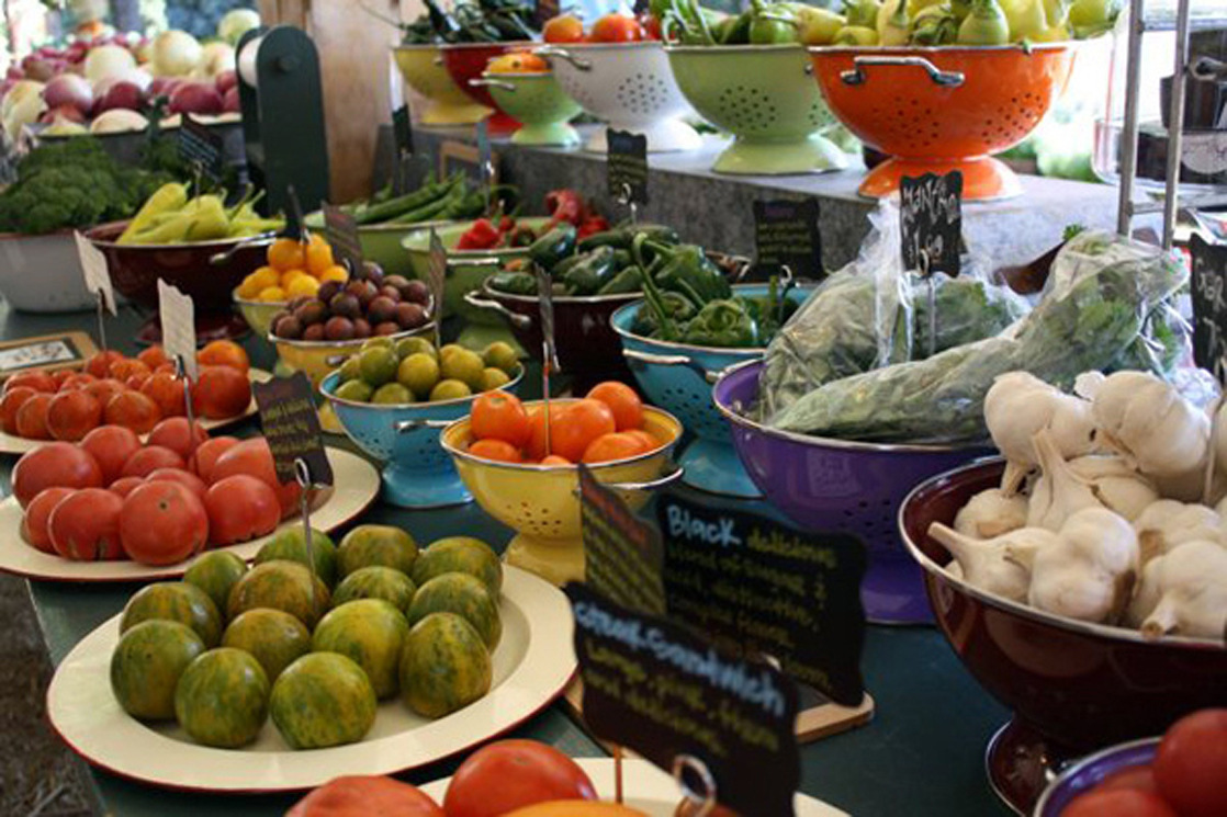 Photo shows a variety of fresh vegetables being sold at a market.