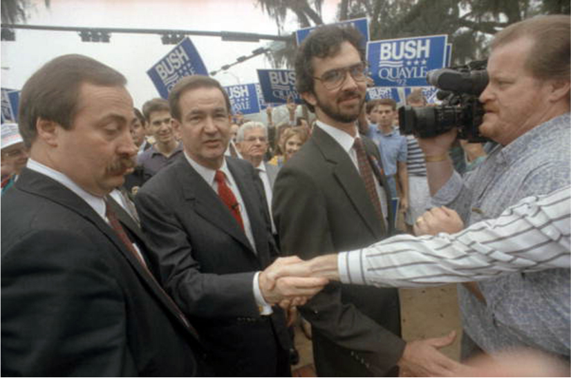 Pat Buchanan shakes hands with someone in the crowd. A crowd behind him holds campaign signs that say