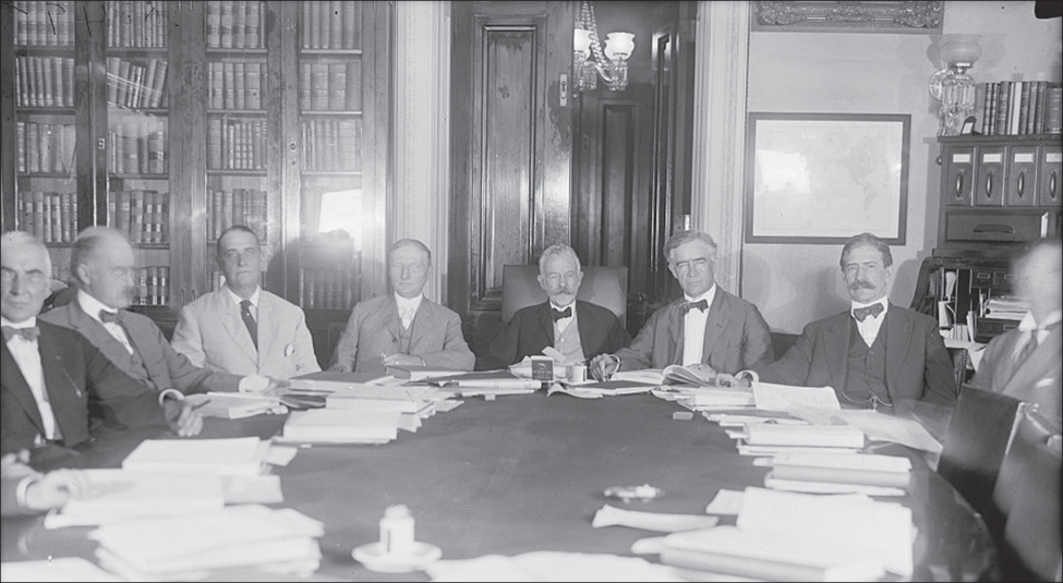 A group of men sit around an oval table that is covered in papers.