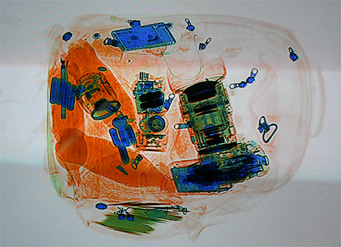 A colored X-ray image of a piece of luggage.