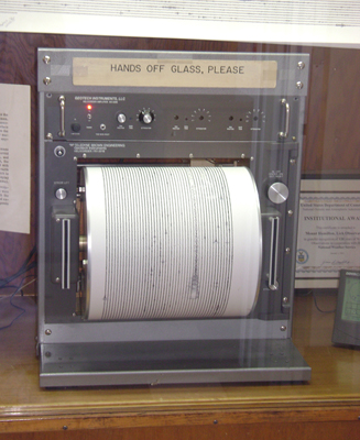 """The figure shows a seismograph put on a wooden table. Its top is labeled as """"Hands off glass, please"""". Below it there are some buttons are shown and a paper roller is fitted in the seismograph to print the observation by the machine. On the right and left of the roller, two vertical cable slots are given."""