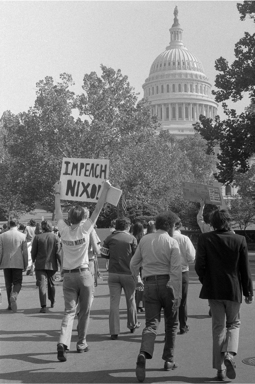 "A group of people walk towards the Capitol. One man wears a shirt and holds a sign that both say ""Impeach Nixon."""