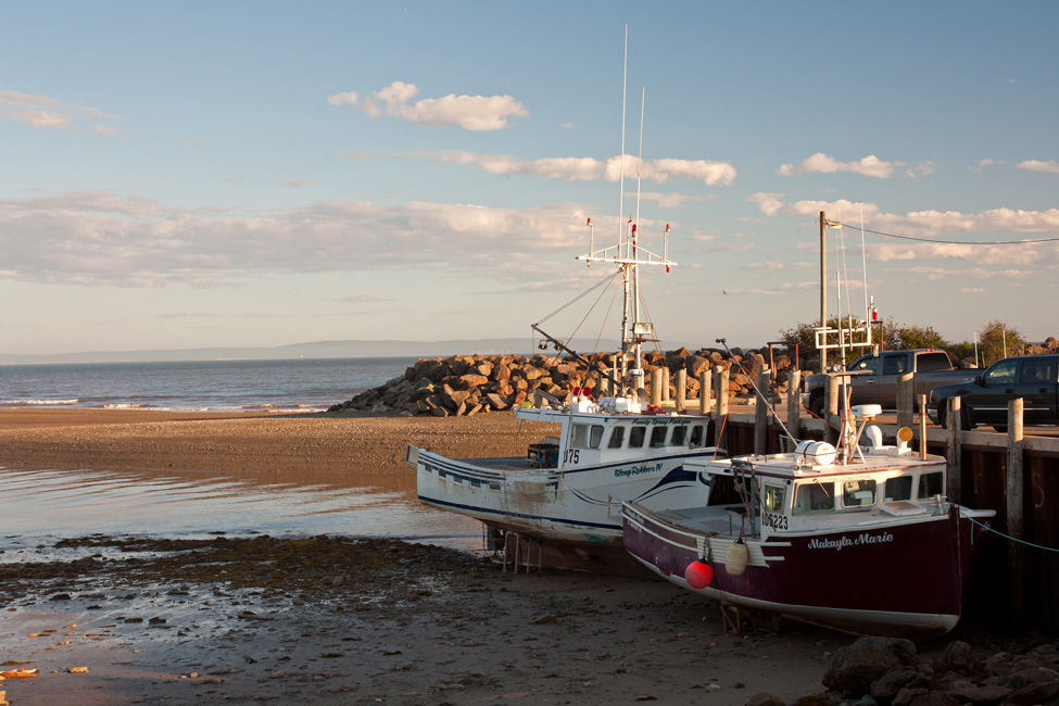 Two boats at a dock during low tide