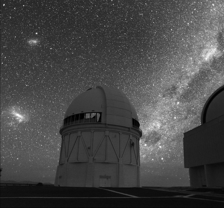 Photograph of the 4-meter telescope at Cerro Tololo Inter-American Observatory silhouetted against the southern sky. The Milky Way is seen to the right of the dome. The Large and Small Magellanic Clouds are seen to the left.