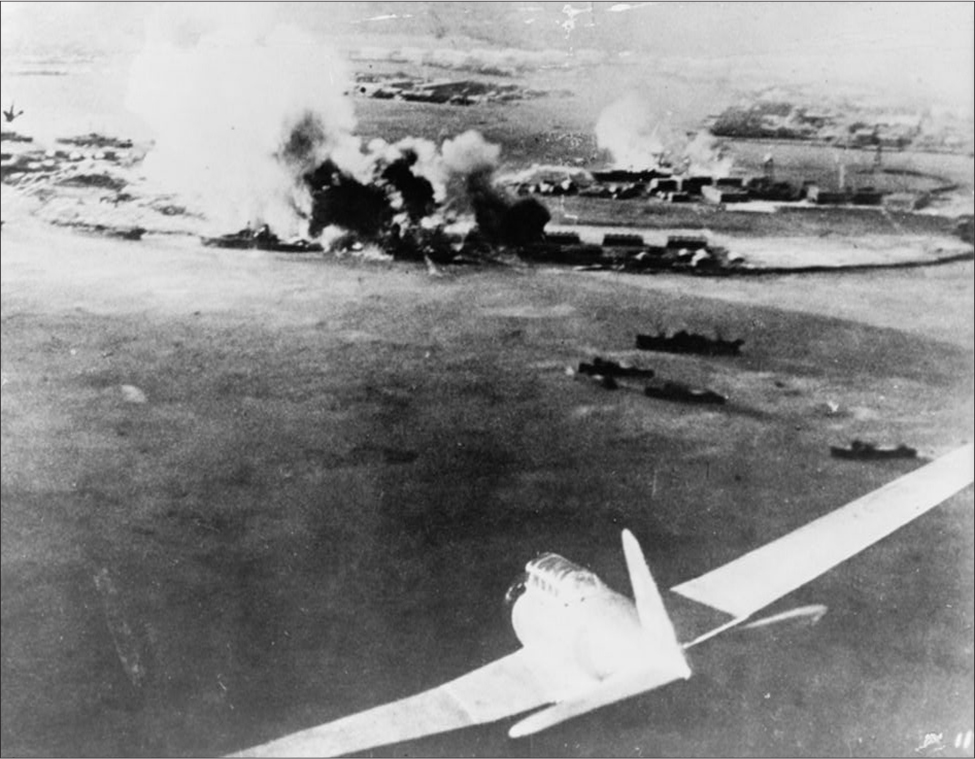 The aerial shot shows a plane flying in the foreground. In the background, smoke rises from multiple explosions.
