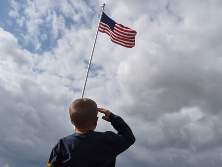 A young boy is shown from behind saluting the American flag flying from a flagpole.
